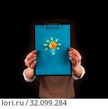 Business man holding a clipboard with a hand drawn light bulb on it. Стоковое фото, фотограф Zoonar.com/Andreas Berheide / easy Fotostock / Фотобанк Лори