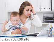 Perplexed mother with child is having issue while working behind laptop. Стоковое фото, фотограф Яков Филимонов / Фотобанк Лори