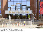 Купить «Saratov region, Russia - 08/25/2019: Facade and signboard of the new modern building of the Kiselyov Theater for Young Spectators, a landmark of the city. Children bathe in the fountain in summer and ride scooters», фото № 32104836, снято 25 августа 2019 г. (c) Светлана Евграфова / Фотобанк Лори