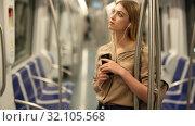 Купить «Young woman with a smartphone and headphones enters a subway car», видеоролик № 32105568, снято 31 марта 2019 г. (c) Яков Филимонов / Фотобанк Лори