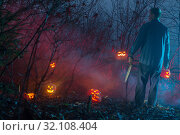 Купить «scary man in night forest is cutting Halloween pumpkins», фото № 32108404, снято 10 ноября 2018 г. (c) Майя Крученкова / Фотобанк Лори