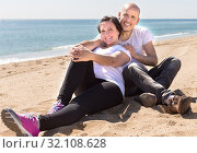 couple of man and a middle-aged woman in white T-shirt sitting on the beach. Стоковое фото, фотограф Татьяна Яцевич / Фотобанк Лори