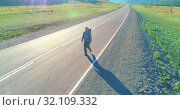 Купить «Flight over hitchhiker tourist walking on asphalt road. Huge rural valley at summer day. Backpack hiking guy.», видеоролик № 32109332, снято 31 июля 2018 г. (c) Александр Маркин / Фотобанк Лори