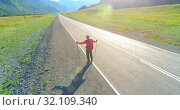 Купить «Flight over hitchhiker tourist walking on asphalt road. Huge rural valley at summer day. Backpack hiking guy.», видеоролик № 32109340, снято 3 августа 2018 г. (c) Александр Маркин / Фотобанк Лори