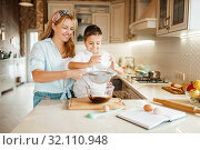 Купить «Mother with son mixing melted chocolate in a bowl», фото № 32110948, снято 6 марта 2019 г. (c) Tryapitsyn Sergiy / Фотобанк Лори