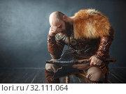 Купить «Sad viking with axe sitting on chair», фото № 32111064, снято 27 марта 2019 г. (c) Tryapitsyn Sergiy / Фотобанк Лори