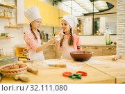 Купить «Little girls cooks in caps tastes vanilla powder», фото № 32111080, снято 30 марта 2019 г. (c) Tryapitsyn Sergiy / Фотобанк Лори
