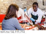 Купить «Salesman serving customer raw fish», фото № 32111772, снято 17 октября 2018 г. (c) Яков Филимонов / Фотобанк Лори