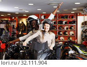 Купить «Couple sitting together on new motorcycle in store and having fun», фото № 32111904, снято 16 января 2019 г. (c) Яков Филимонов / Фотобанк Лори
