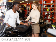 Купить «Polite smiling female seller communicating with male customer in modern motorcycle salon», фото № 32111908, снято 16 января 2019 г. (c) Яков Филимонов / Фотобанк Лори