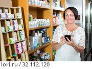 Купить «Smiling mature woman customer holding mobile phone», фото № 32112120, снято 21 сентября 2019 г. (c) Яков Филимонов / Фотобанк Лори