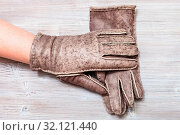 Workshop on sewing gloves - top view of female hand in new hand-made glove on wooden background. Стоковое фото, фотограф Zoonar.com/Valery Voennyy / easy Fotostock / Фотобанк Лори