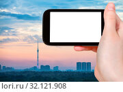 Travel concept - tourist photographs Moscow city skyline with Ostankinskaya TV Tower in Russia in sunrize on smartphone with cut out screen for advertising logo. Стоковое фото, фотограф Zoonar.com/Valery Voennyy / easy Fotostock / Фотобанк Лори