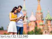 Young dating couple in love walking in city background St Basils Church. Стоковое фото, фотограф Дмитрий Травников / Фотобанк Лори