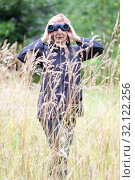 Купить «Blond woman with binoculars peeks out from behind tall grass, ornithologist observes a birds in nature», фото № 32122256, снято 11 августа 2019 г. (c) Кекяляйнен Андрей / Фотобанк Лори