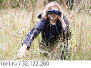 Женщина наблюдает в бинокль, раздвинув рукой высокую траву. Стоковое фото, фотограф Кекяляйнен Андрей / Фотобанк Лори