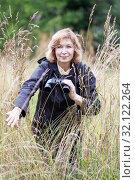 Женщина с биноклем стоит в траве на болоте. Стоковое фото, фотограф Кекяляйнен Андрей / Фотобанк Лори