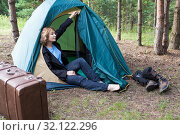 Купить «Middle age woman resting in camping tent after hiking route, old fahioned suitcase and boots», фото № 32122296, снято 11 августа 2019 г. (c) Кекяляйнен Андрей / Фотобанк Лори