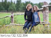 Mature mother and teenage daughter portrait on countryside, sitting together on wooden fence in farm meadow. Стоковое фото, фотограф Кекяляйнен Андрей / Фотобанк Лори