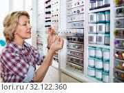 Mature glad woman customer picking various buttons. Стоковое фото, фотограф Яков Филимонов / Фотобанк Лори