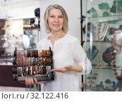 Купить «Smiling woman seller offering fashionable bracelets in the store», фото № 32122416, снято 2 мая 2019 г. (c) Яков Филимонов / Фотобанк Лори