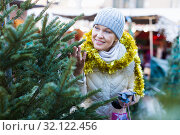 Купить «Smiling woman is buying Christmas tree in the market», фото № 32122456, снято 21 декабря 2017 г. (c) Яков Филимонов / Фотобанк Лори