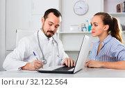 Купить «Female visitor consulting man doctor in hospital», фото № 32122564, снято 12 ноября 2019 г. (c) Яков Филимонов / Фотобанк Лори