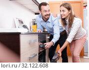 Купить «Couple choosing household appliances for kitchen», фото № 32122608, снято 11 апреля 2018 г. (c) Яков Филимонов / Фотобанк Лори