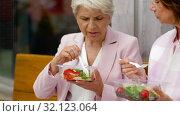 senior women eating takeaway food on city street. Стоковое видео, видеограф Syda Productions / Фотобанк Лори
