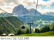 """Italy 19.06.2019: cabin of Cable car lift """"Col raiser"""" arrive to top of the mountain with place of rest, restaurant and hotel in summer sunny day. Selva di Val Gardena Trentino, Alto Adige, Dolomites. Стоковое фото, фотограф Алексей Ширманов / Фотобанк Лори"""