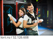 Купить «Man and woman standing back to back with laser pistols», фото № 32126608, снято 25 апреля 2018 г. (c) Яков Филимонов / Фотобанк Лори