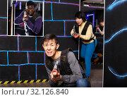 Купить «Chinese man during lasertag game in dark room», фото № 32126840, снято 23 января 2019 г. (c) Яков Филимонов / Фотобанк Лори