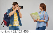 Купить «happy couple of tourists with backpacks and camera», фото № 32127456, снято 17 марта 2019 г. (c) Syda Productions / Фотобанк Лори