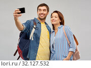 Купить «couple of tourists taking selfie by smartphone», фото № 32127532, снято 17 марта 2019 г. (c) Syda Productions / Фотобанк Лори