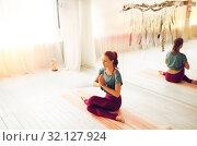 Купить «woman meditating at yoga studio», фото № 32127924, снято 21 июня 2018 г. (c) Syda Productions / Фотобанк Лори