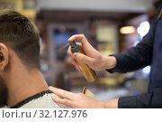 Купить «barber applying styling spray to male hair at shop», фото № 32127976, снято 6 апреля 2017 г. (c) Syda Productions / Фотобанк Лори