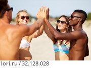 Купить «happy friends making high five on summer beach», фото № 32128028, снято 29 июля 2018 г. (c) Syda Productions / Фотобанк Лори