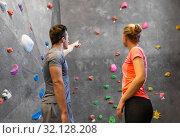 Купить «man and woman exercising at indoor climbing gym», фото № 32128208, снято 2 марта 2017 г. (c) Syda Productions / Фотобанк Лори