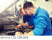 mechanic men with wrench repairing car at workshop. Стоковое фото, фотограф Syda Productions / Фотобанк Лори
