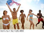 Купить «happy friends with american flag on summer beach», фото № 32128480, снято 29 июля 2018 г. (c) Syda Productions / Фотобанк Лори