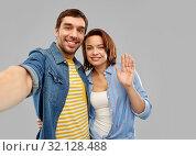 happy couple taking selfie over grey background. Стоковое фото, фотограф Syda Productions / Фотобанк Лори