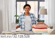 Купить «african american woman with ironed linen at home», фото № 32128528, снято 7 апреля 2019 г. (c) Syda Productions / Фотобанк Лори