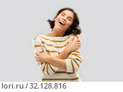 happy woman in striped pullover hugging herself. Стоковое фото, фотограф Syda Productions / Фотобанк Лори