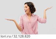 Купить «young woman in striped shirt holding something», фото № 32128820, снято 6 марта 2019 г. (c) Syda Productions / Фотобанк Лори