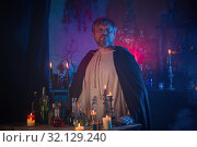 Купить «portrait of wizard with burning candles and magic potions», фото № 32129240, снято 14 августа 2019 г. (c) Майя Крученкова / Фотобанк Лори