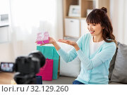Купить «asian female blogger with gift bag recording video», фото № 32129260, снято 13 апреля 2019 г. (c) Syda Productions / Фотобанк Лори
