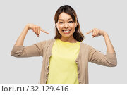 Купить «happy asian woman over grey background», фото № 32129416, снято 11 мая 2019 г. (c) Syda Productions / Фотобанк Лори