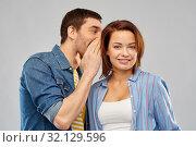 Купить «happy couple whispering over grey background», фото № 32129596, снято 17 марта 2019 г. (c) Syda Productions / Фотобанк Лори