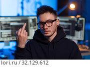 Купить «hacker with computers showing middle finger», фото № 32129612, снято 27 марта 2019 г. (c) Syda Productions / Фотобанк Лори