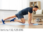 man doing running plank exercise at home. Стоковое фото, фотограф Syda Productions / Фотобанк Лори